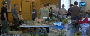 PolyCon attendees gather around a large table covered in miniature landscapes ranging from oceans, frozen tundra, humid jungles, and barren wastelands.